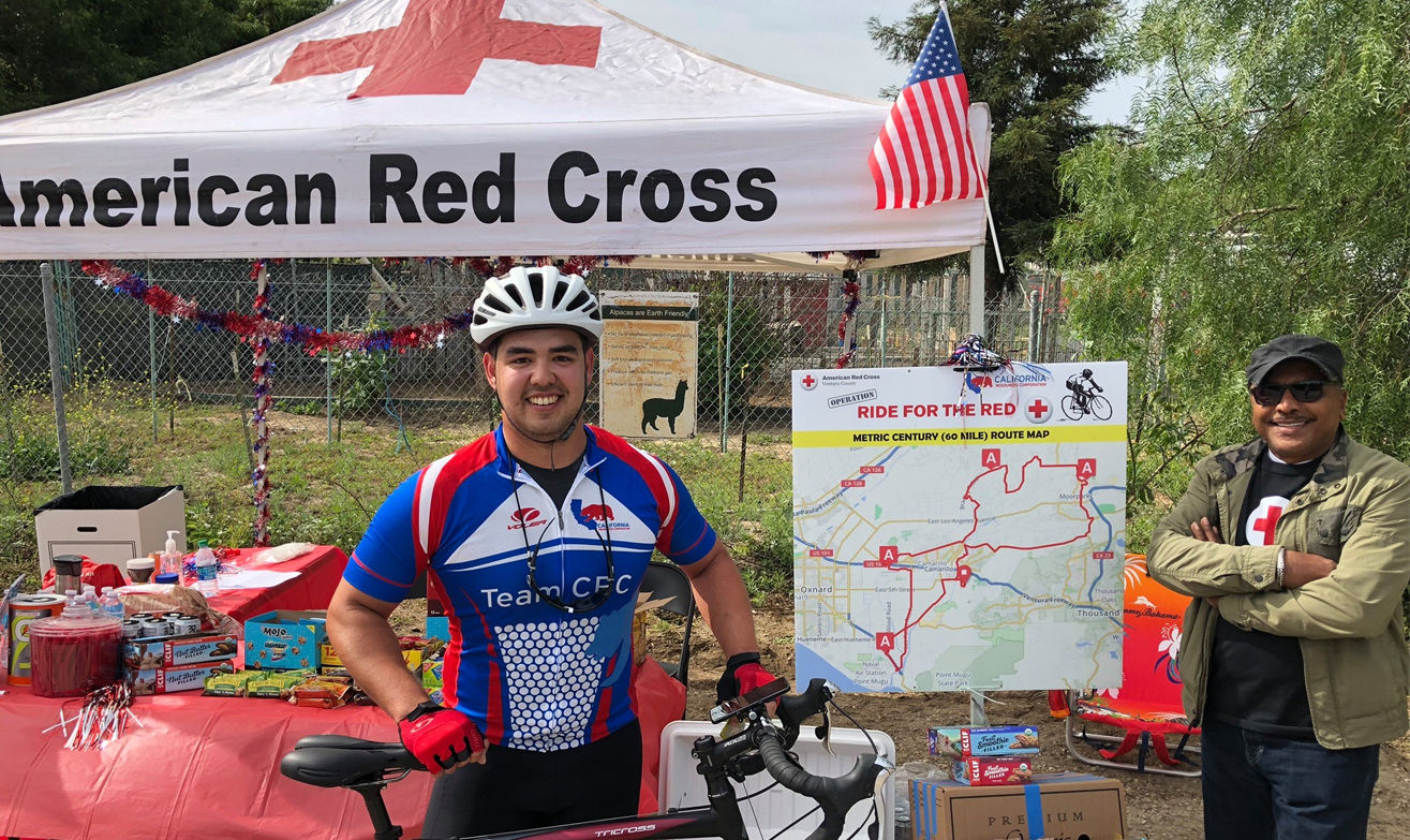 Photo of Bicyclist in front of Red Cross Tent