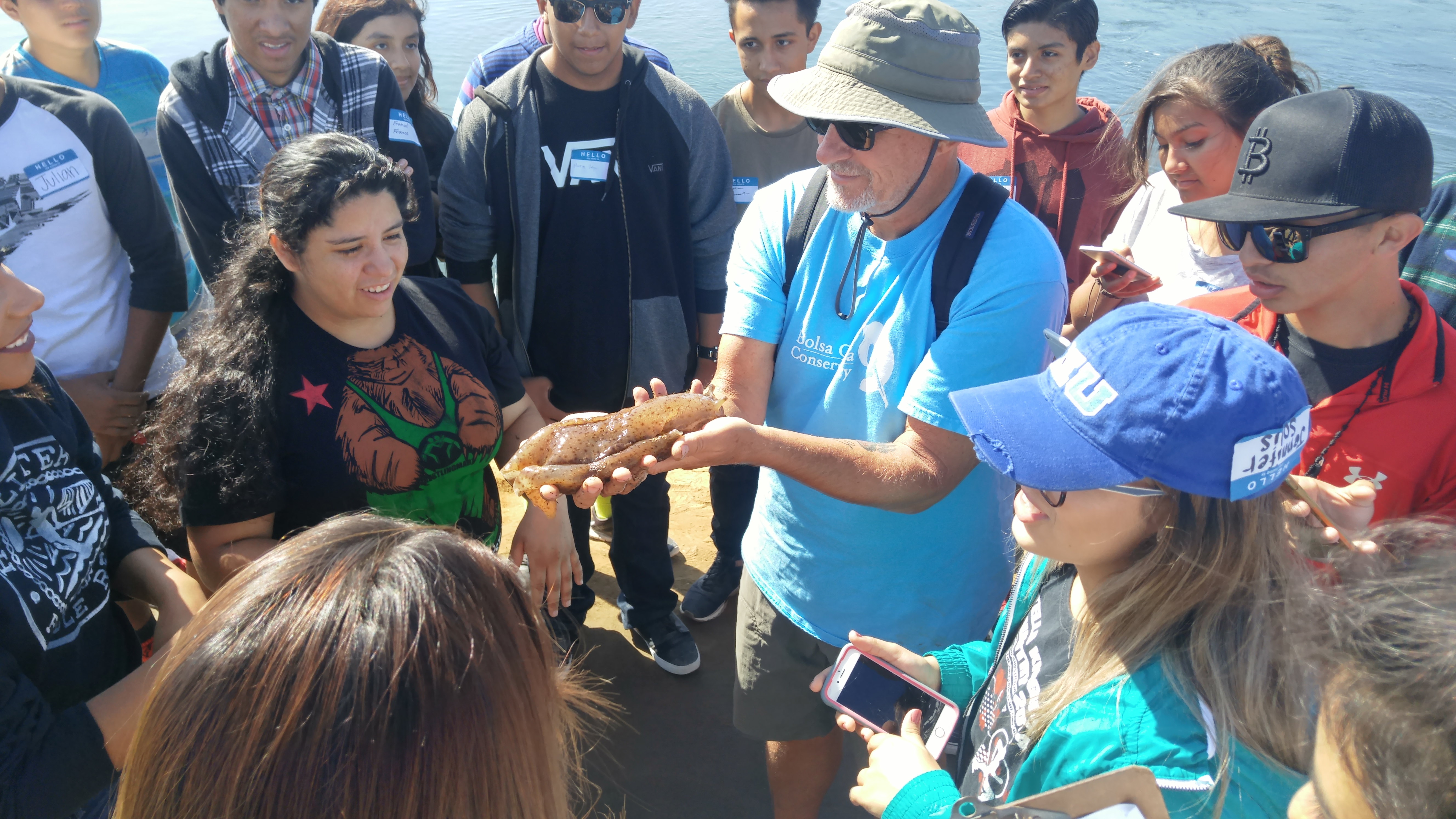 A group of students gather around to learn about a sea creature at Bolsa Chica Conservancy