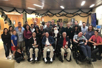 CRC members and volunteers posing with veterans after decorating the Long Beach Spinal Cord Injury Long Term Care Unit