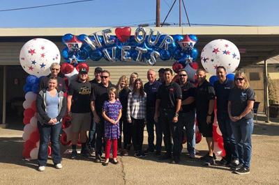 Members of CRC and US Vets posing beneath a baloon display in Long Beach