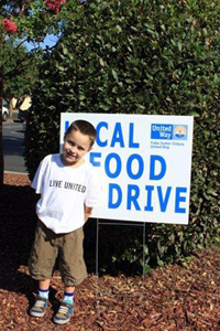 A child poses in front of a Yuba-Sutter-Colusa United Way local food drive sign