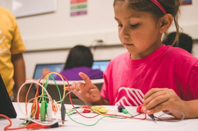 Photo of child with colored wires learning about electric currents
