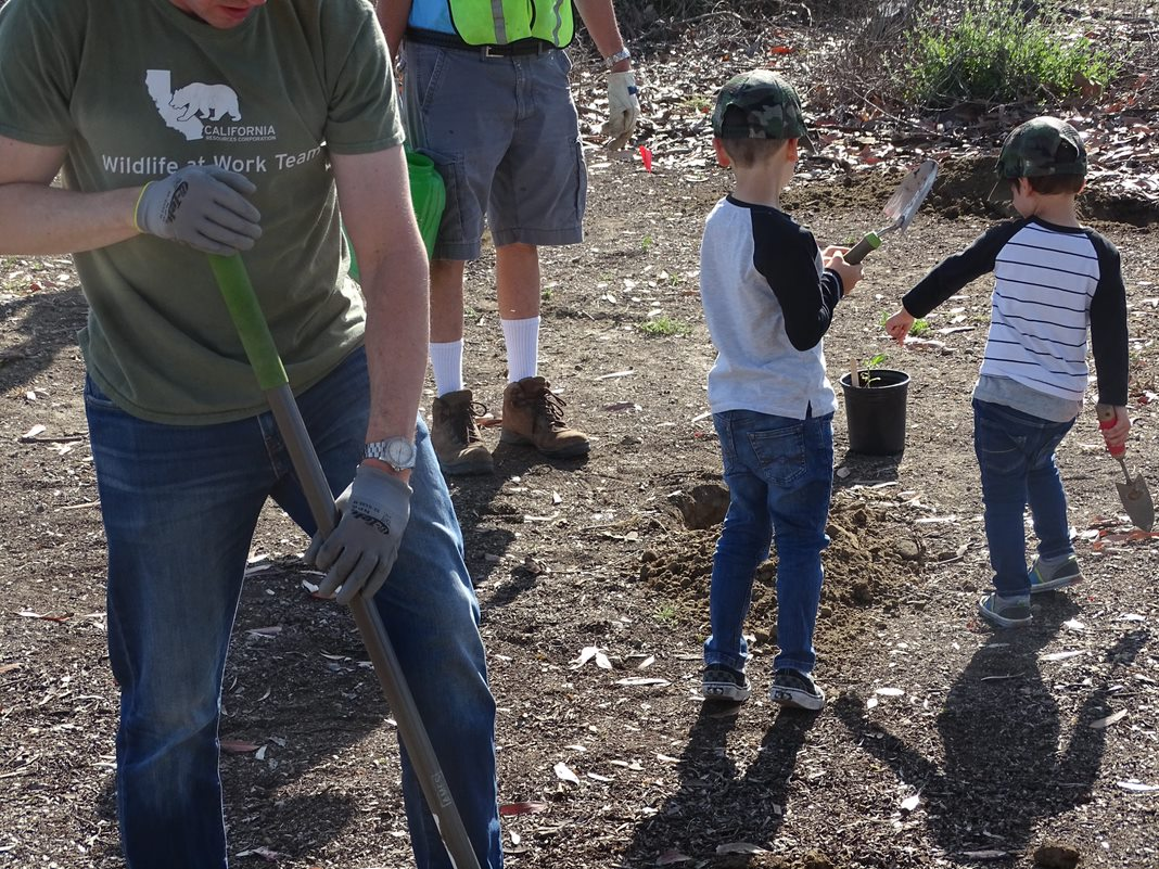 Photo of CRC employee and children performing work at the Bolsa Chica Ecological Reserve